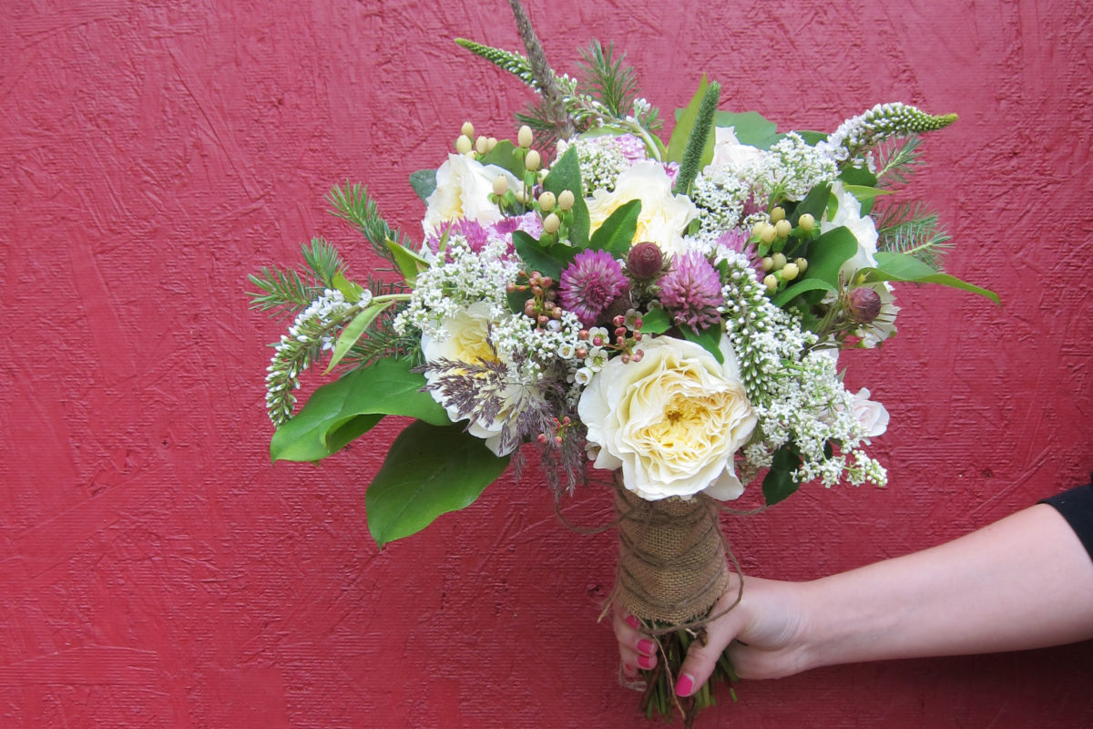 Wild Alaska bridal bouquet with garden roses, lavender button mums, wildflowers, alder, spruce, salal, seeded eucalyptus and a four-leaf clover | designed by Natasha Price of Paper Peony Alaska