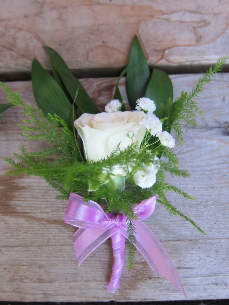 Boutonniere made with white rose, Italian ruscus and plumosa fern | designed by Natasha Price of alaskaknitnat.com
