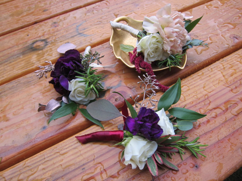 Boutonniere made with white spray roses, purple mini carnations, pink amaranthus, rosemary, gold eucalyptus and Italian ruscus | designed by Natasha Price of alaskaknitnat.com
