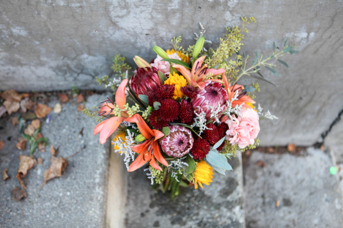 Rustic wedding bouquet made with protea, mini sunflowers, orange lilies, carnations, burgundy button mums, eucalyptus and limonium | designed by Natasha Price of Alaskaknitnat.com