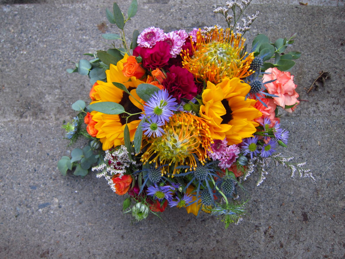 Alaska Weddings: a bridal bouquet made with sunflower, protea, mini carnation, button mums, mini asters, limonium and eucalyptus. Just perfect for a lakeside wedding. Designed by Natasha Price of Paper Peony Alaska
