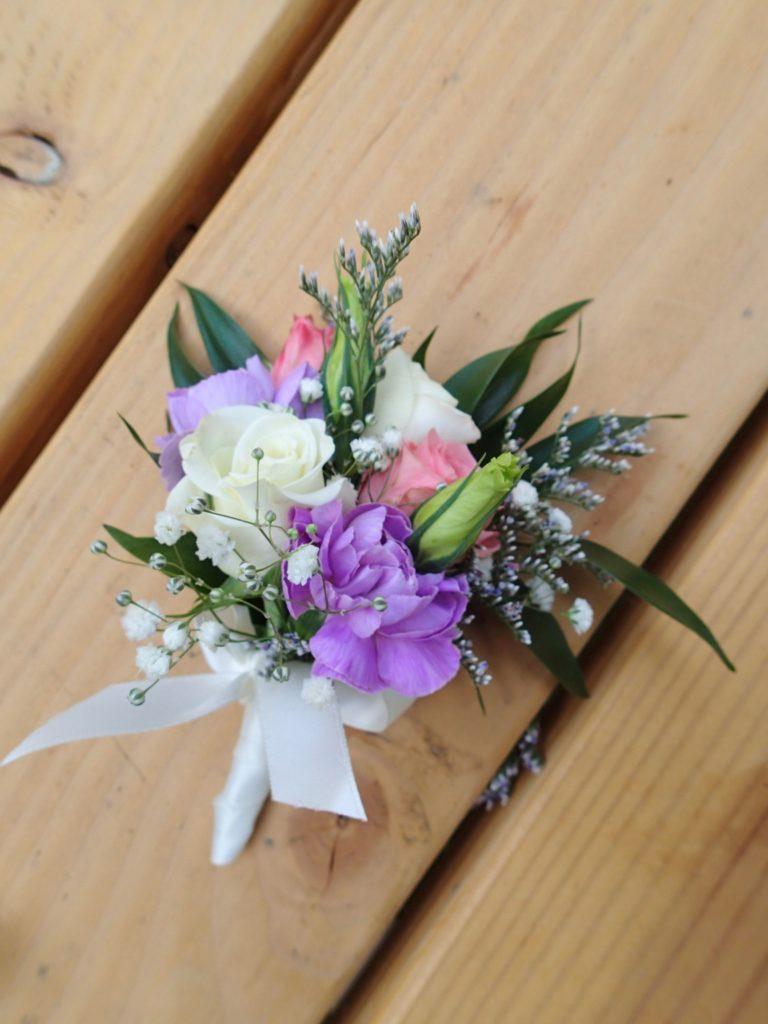 Lapel corsage made with spray roses, lavender mini carnations, limonium, baby's breath and Italian ruscus. Designed by Natasha Price of Alaskaknitnat.com