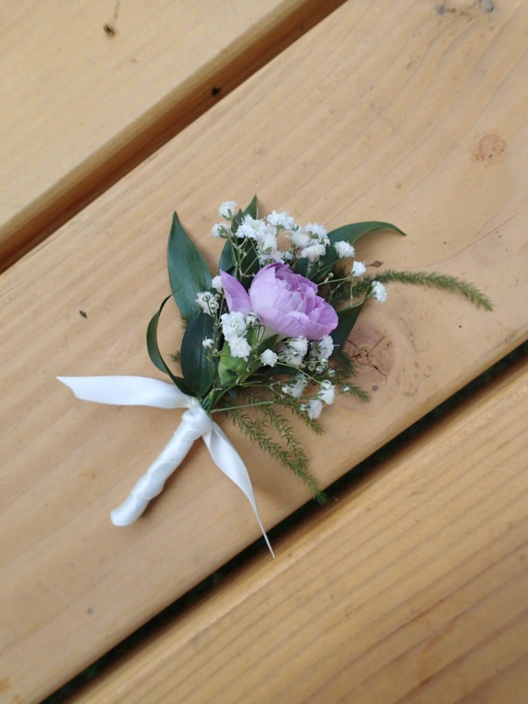 Lavender mini carnation boutonniere with Italian ruscus and baby's breath. Designed by Natasha Price of alaskaknitnat.com