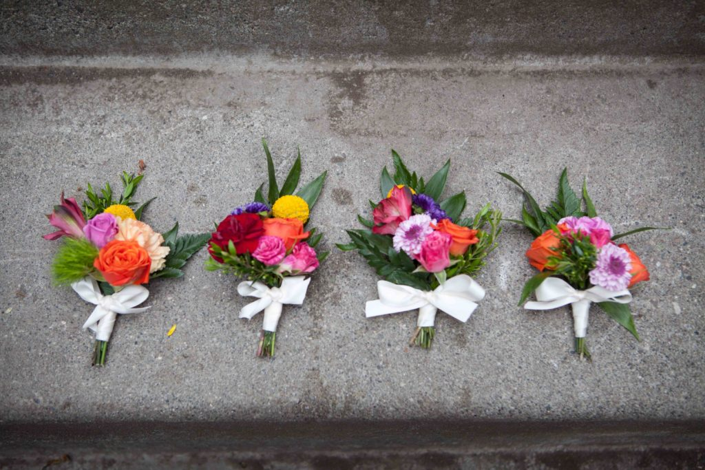 Boutonnieres made with lavender button mums, scarlet mini carnations, red alstroemeria, billy balls and orange and pink spray roses | designed by Natasha Price of Paper Peony Alaska