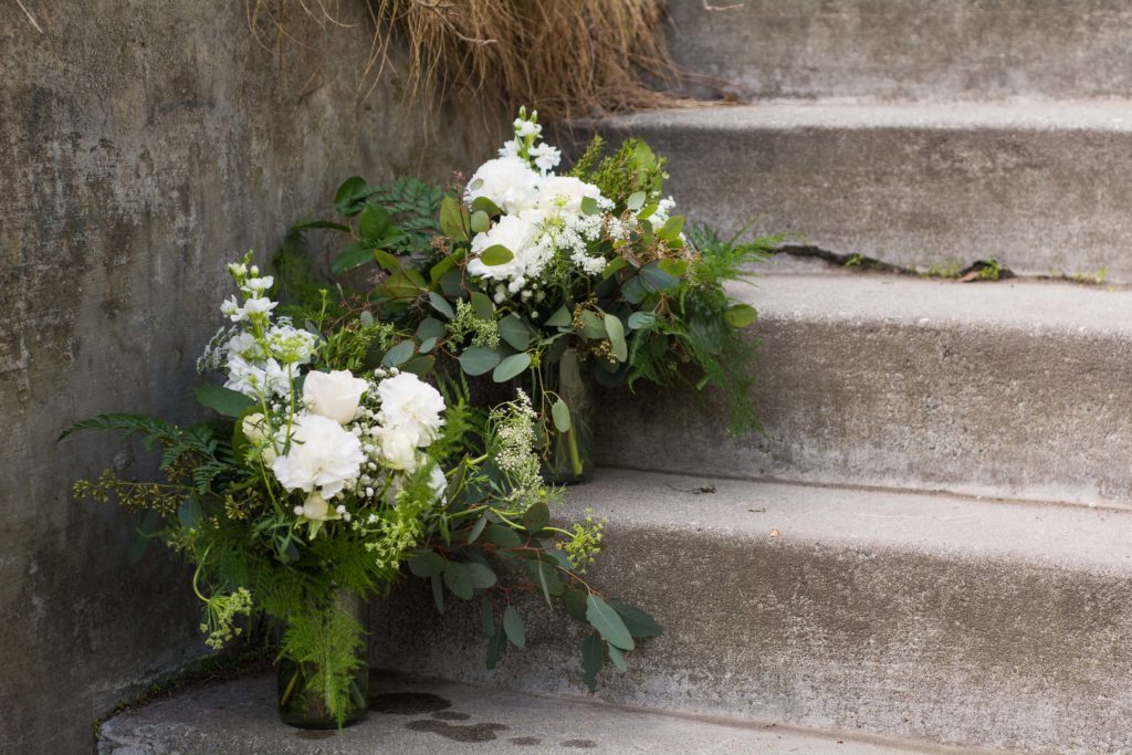 Centerpieces with white roses, carnations and eucalyptus | designed by Natasha Price and photo by Sean Carpenter