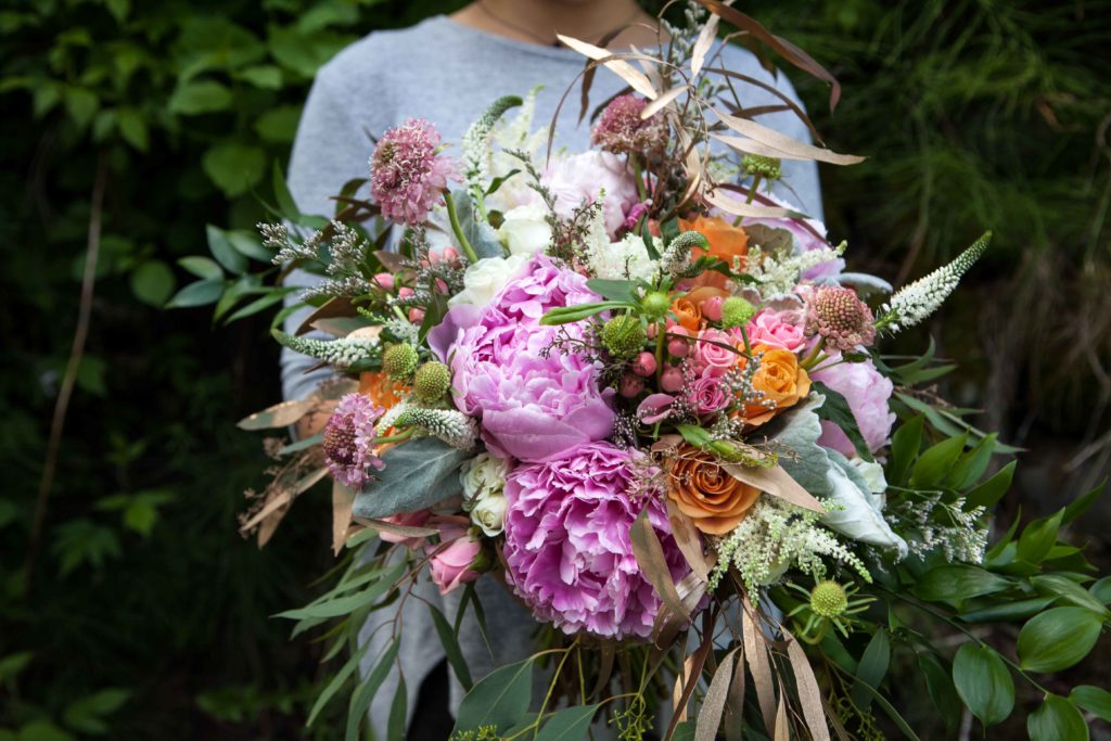 Wild bridal bouquet with peonies, roses, veronica, astilbe, scabiosa, dusty miller and eucalyptus | designed by Natasha Price of Paper Peony Alaska